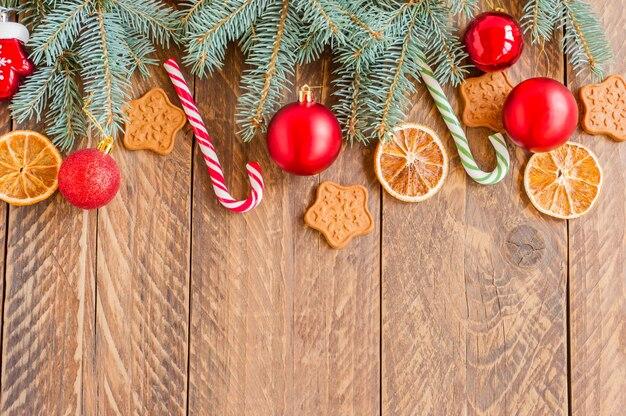 Branches de sapin de noël avec des boules, des cannes de bonbon, des oranges sèches et des biscuits en forme d'étoile sur fond en bois avec espace de copie.