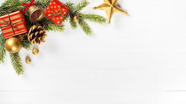 Branches de sapin de noël cône de pin or jingle bell et coffrets cadeaux sur fond de bois blanc.