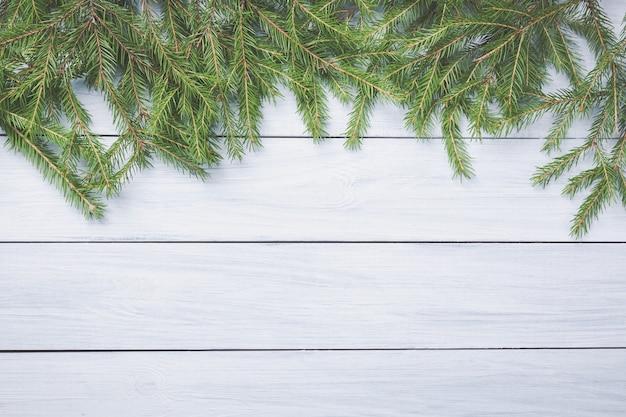 Branches de sapin de noël sur le dessus d'une planche de bois blanche.