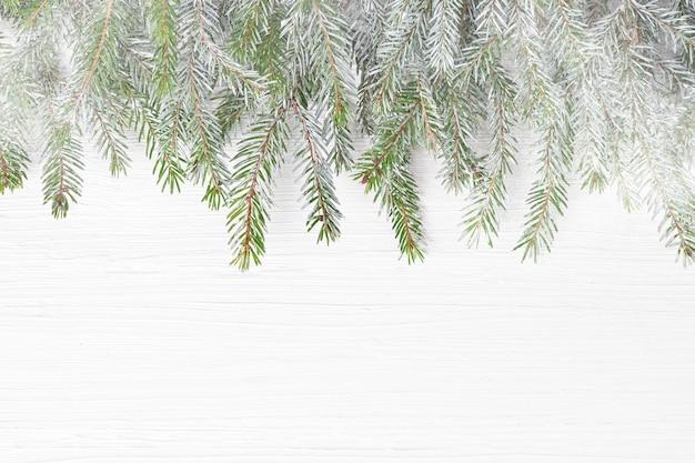 Branches de sapin de noël avec de la neige sur un fond en bois blanc. espace de copie, vue de dessus