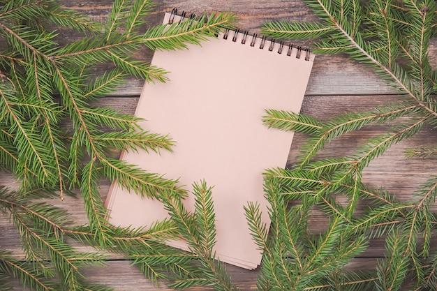 Branches de sapin de noël sur planche de bois avec cahier vierge.