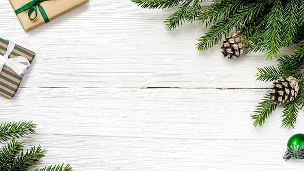 Branches de sapin de noël, pommes de pin et cadeaux sur fond rustique en bois blanc. vue de dessus, espace de copie