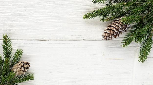 Branches de sapin de noël et pommes de pin sur fond de bois blanc ancien.
