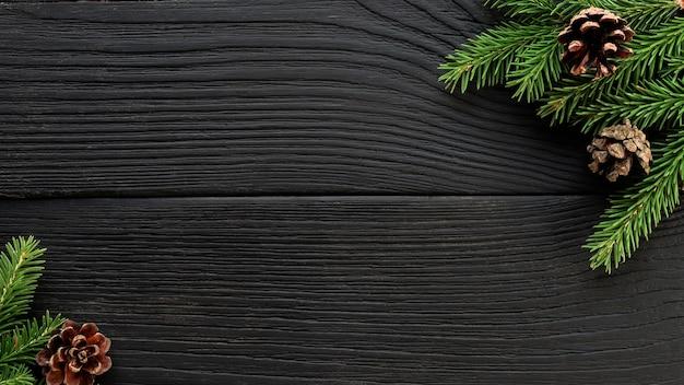 Branches de sapin de noël et pommes de pin sur un fond en bois noir.