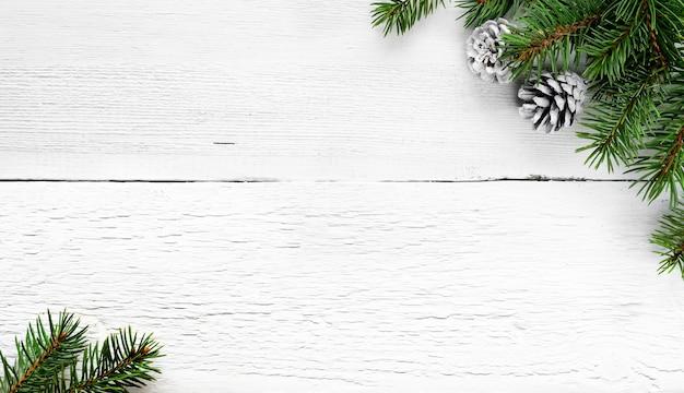 Branches de sapin de noël et pommes de pin sur fond rural en bois blanc.