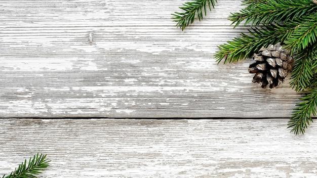 Branches de sapin de noël et pommes de pin sur fond rustique en bois blanc minable.