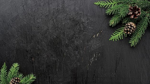 Branches de sapin de noël et pommes de pin sur une planche de bois noire