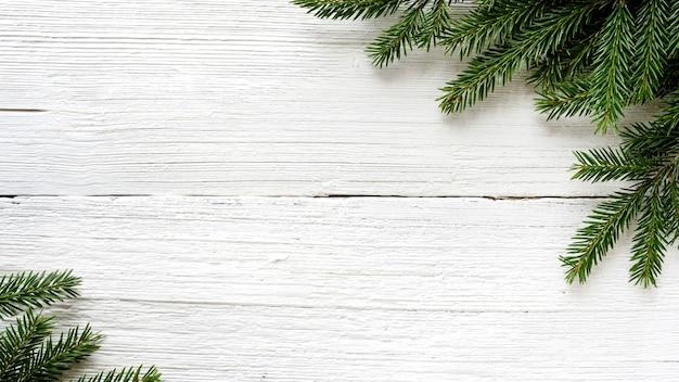 Branches de sapin sur planche rustique en bois blanc. fond de noël.