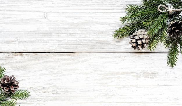 Branches de sapin et pommes de pin sur fond de noël de planche de bois blanc.
