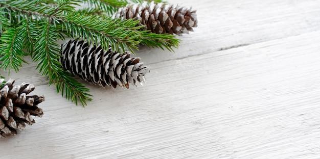 Branches de sapin et pommes de pin sur fond rustique en bois blanc.