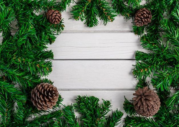 Branches de sapin et pommes de pin sur planche de bois blanc