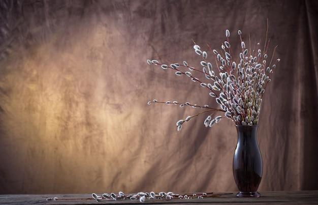 Branches de saule dans un vase en verre sur fond brun foncé