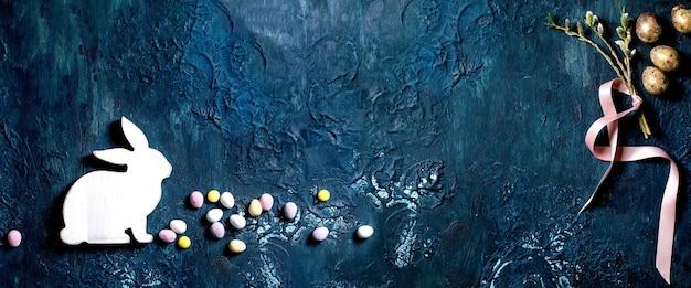 Branches de saule de fleur de pâques, oeufs de caille dorés, lapin en bois sur table de texture bleue classique. mise à plat, copiez l'espace. inscription de joyeuses pâques