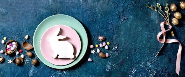 Branches de saule de fleurs de pâques, œufs de caille dorés, lapin en bois et assiettes vides sur table de texture bleue classique. mise à plat, copiez l'espace. inscription de joyeuses pâques