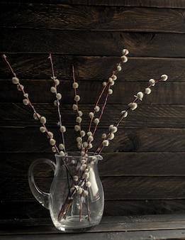 Branches d'un saule à fleurs se tiennent dans un bocal en verre foncé sur un fond