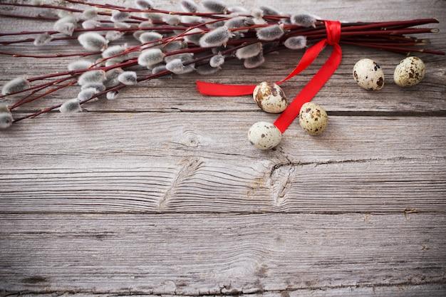 Branches de saule avec des œufs sur un fond en bois