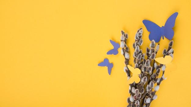 Branches de saule avec des papillons de papier sur une table jaune