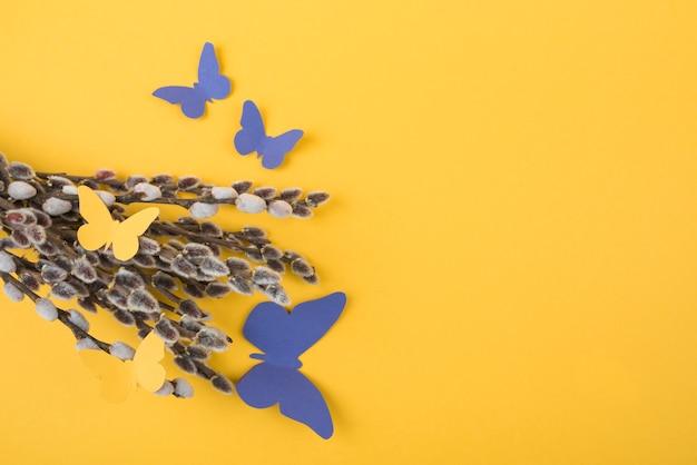 Branches de saule avec des papillons de papier sur la table
