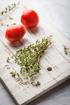 Branches de thym et deux tomates sur un fond clair