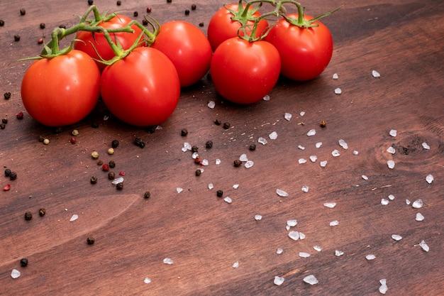 Branches de tomate éparpillée de sel et de poivre noir en poudre sur pierre brune