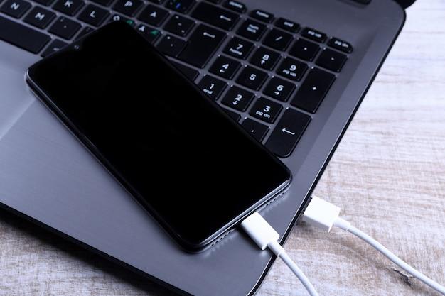 Branchez le cordon usb, le chargeur de câble, la charge, le chargement et le transfert de données du téléphone mobile, du smartphone avec un ordinateur portable sur le plancher en bois, de la table vue de dessus