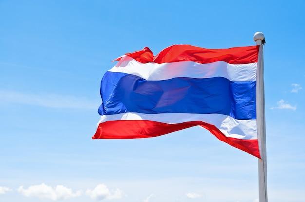 Brandir le drapeau thaïlandais dans le vent sur fond de ciel