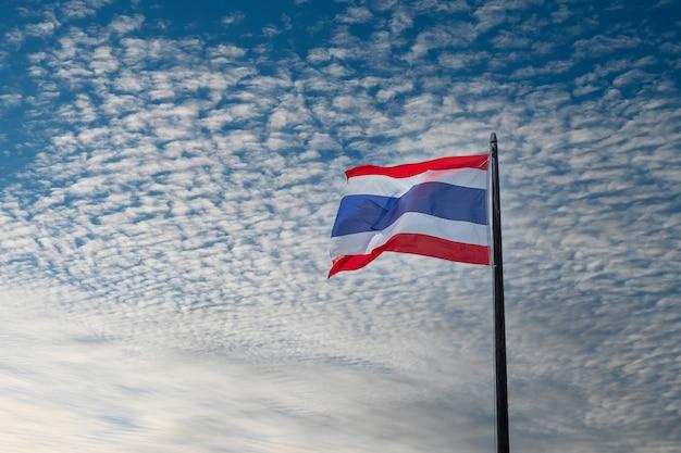 Brandir le drapeau de la thaïlande sur fond de ciel bleu