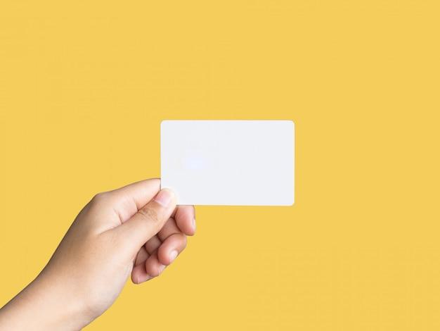 Brandissant une maquette de carte de visite blanche sur fond jaune.