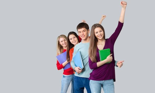 Les bras adultes heureux d'étudiant ont levé de nouveau au sac à dos d'école