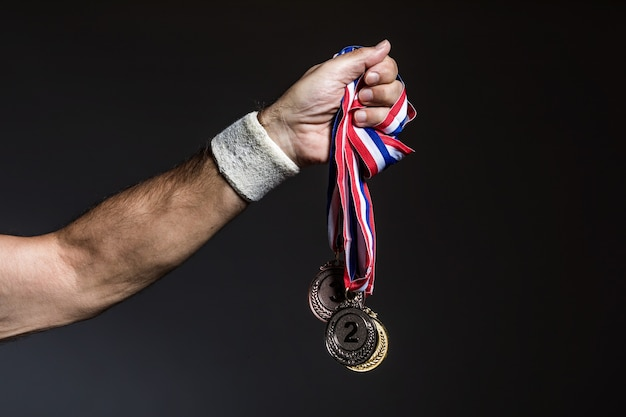 Bras d'athlète âgé tenant trois médailles d'or, d'argent et de bronze sur fond sombre. concept de sport et de victoire.