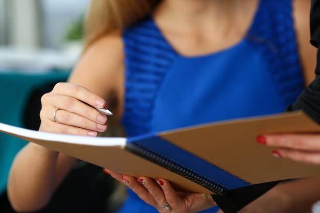 Bras de commis femelle faire des marques dans le bloc-notes avec un stylo argenté