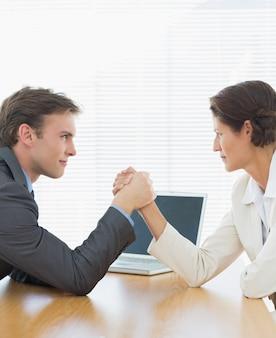 Bras de couple d'affaires de lutte au bureau