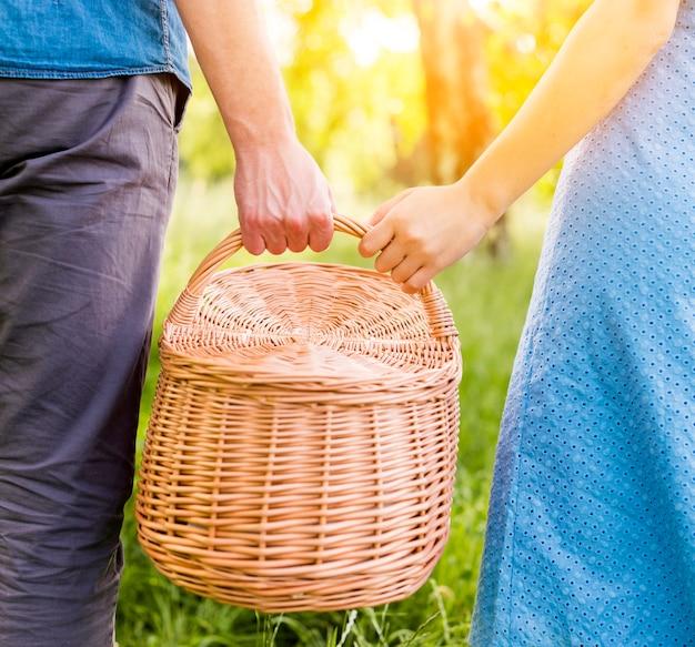 Bras de couple tenant le panier pique-nique dans le parc