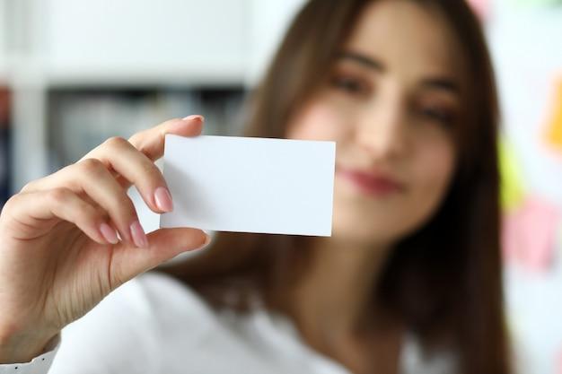 Bras féminin en costume donner carte de visite vierge au visiteur