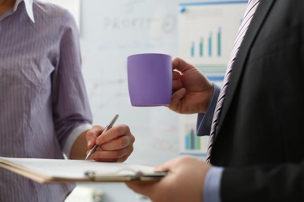 Bras féminin offre une forme de contrat sur un bloc-notes et un stylo argenté pour signer un gros plan grève pour le profit col blanc motivation décision syndicale dirigeant d'entreprise vente agent d'assurance concept