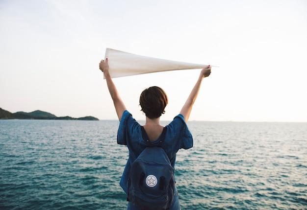 Bras femme, élevé, et, tenue, drapeau, par, les, mer, dans, vue postérieure