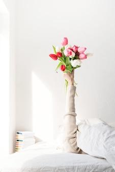 Bras de femme sorti de la couverture tenant un bouquet de fleurs de tulipes. femme au lit tenant des fleurs de tulipes