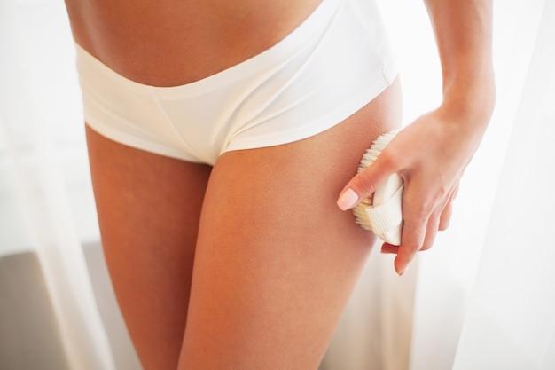 Le bras de la femme tenant une brosse sèche en haut de sa jambe.