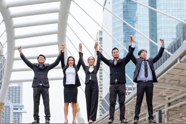 Le bras d'homme d'affaires de groupe professionnel levé est le bonheur avec le succès