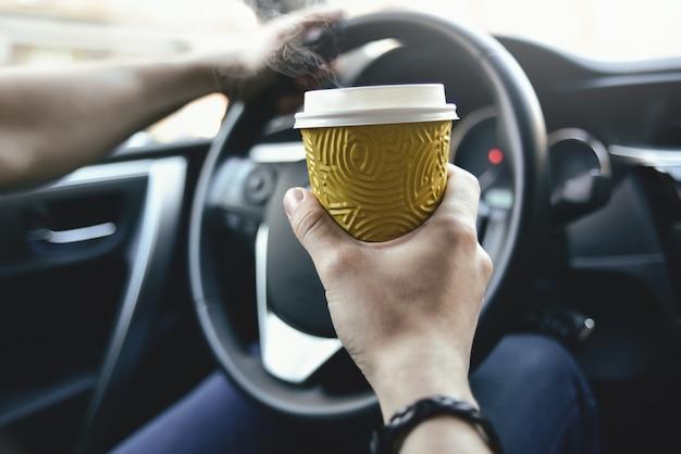 Les bras de l'homme tiennent un café et un gouvernail en automobile