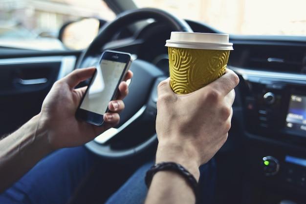 Les bras de l'homme tiennent un café et un téléphone dans une automobile