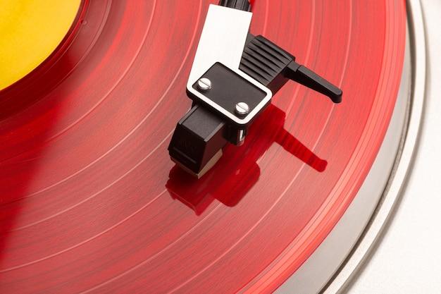 Bras de lecture en gros plan sur le vinyle rouge