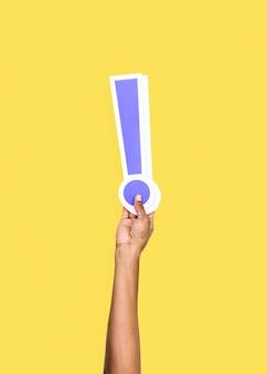 Bras levé et tenant l'icône du point d'exclamation
