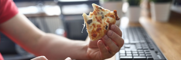Bras mâles prenant un gros morceau de pizza fraîche croustillante