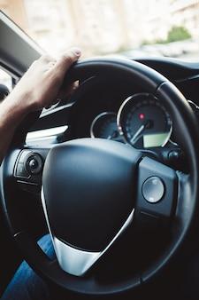 Bras mâles tenant le gouvernail de la voiture en cuir