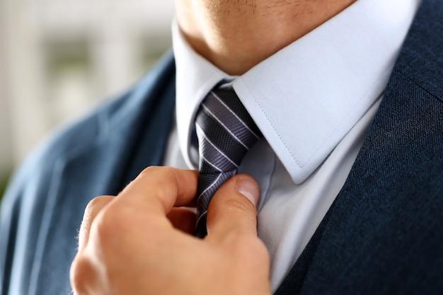 Bras masculin en costume bleu mis cravate closeup
