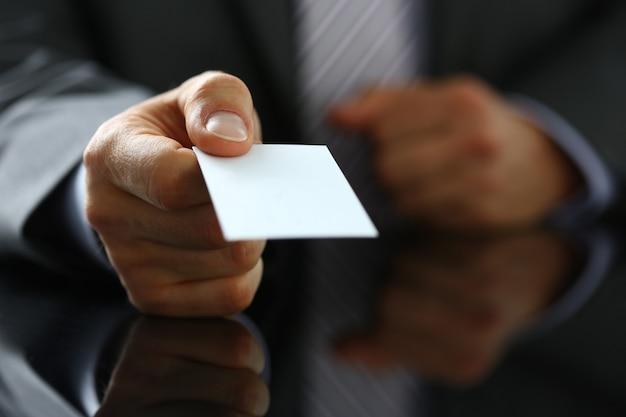 Bras masculin en costume donner carte de visite vierge au visiteur closeup