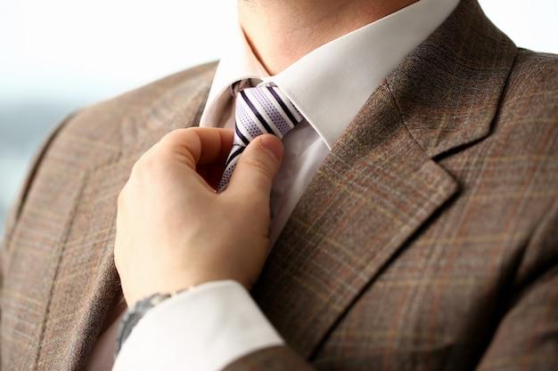 Bras masculin en costume marron cravate closeup