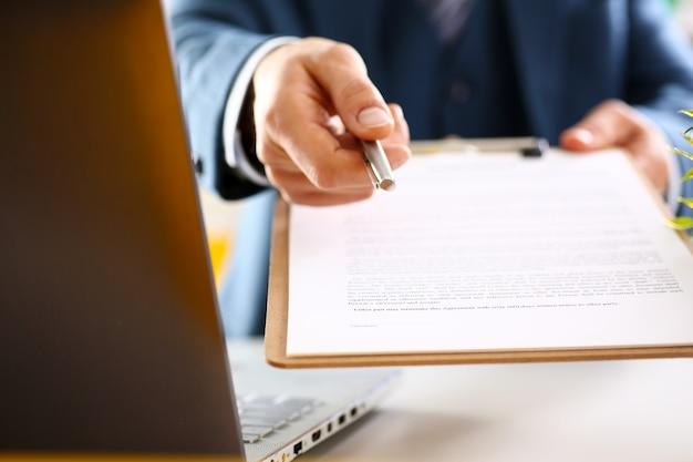 Le bras masculin en costume offre la forme de contrat sur le presse-papiers