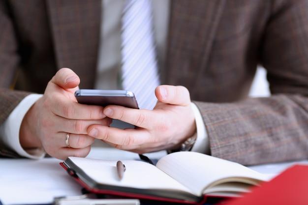 Bras masculin en costume tenir téléphone et stylo argenté